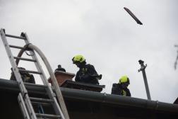Tetőn dolgozó tűzoltó